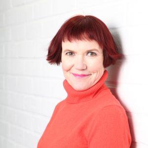 Författaren Rosa Liksom poserar i röd tröja.