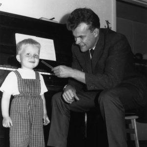 5-v vaaletukkainen poika pianon edessä. Isä istuu vieressä ja soittaa äänirautaa pojan korvalle.