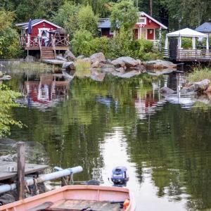 Röda stugor vid vattnet, en träbåt förtöjd vid en brygga.