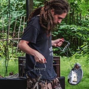Man med långa rastaflätor uppträder med egenhändigt byggda instrument av skrot.