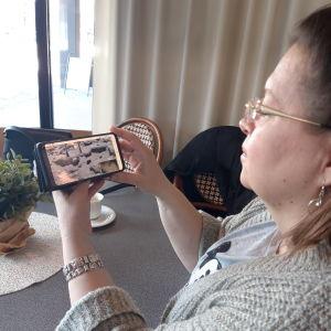 Tiia Kumpumäki katselee kännykältä Yle Luonnon Ahmaliveä.