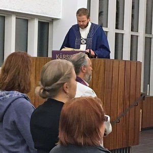 Piispa Teemu Laajasalo lukee raamatuntekstiä kirkossa ja seurakunta seisoo