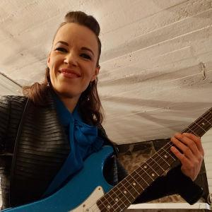 Erja Lyytinen fotat nedrifrån, med gitarr. Ser leende in i kameran.