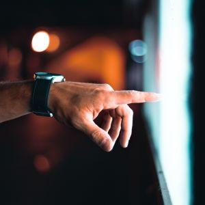 Käsi osoittaa näyttöä tai muuta valoisaa pintaa.