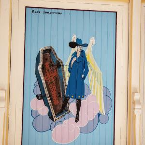 Enkeli pukeutuneena sinisävyisiin muodikkaisiin takkiin ja saappaisiin, taulun yläosassa teksti Kati Josefiina.