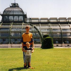 Murrosikäinen ja noin viisivuotias poika Wienissä nurmikentällä