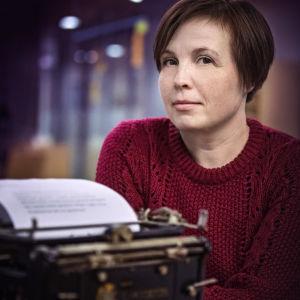 Författaren Karin Erlandsson vid en skrivmaskin.