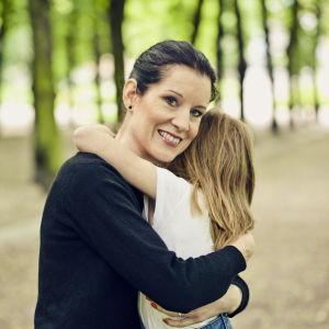 Kvinna ler mot kameran medan hon kramar om ett litet barn