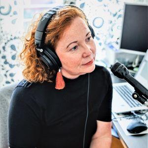 Heidi Finnilä bandar podd och pratar i en mikrofon