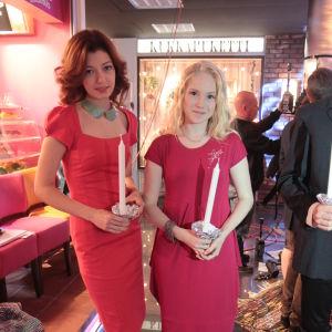 Anni ja Tuija punaisissa mekoissaan, kynttilät käsissään.