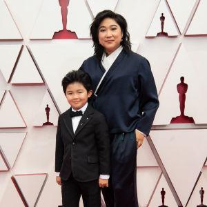 Barnskådespelaren Alan S. Kim från filmen Minari på röda mattan med producenten Christina Oh.