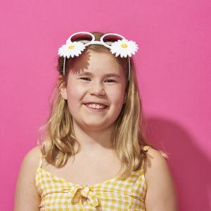 Wilma poserar glatt med blommiga solglasögon på huvudet.