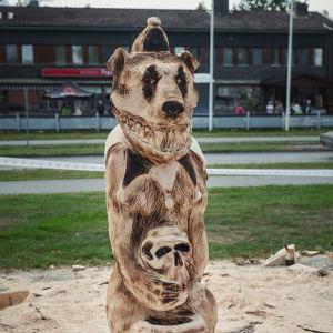 Puusta tehty veistos, karhu sirkusasussa, leveä irvistys, sylissä pääkallo