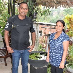 Ett lankesiskt par står på en balkong och ser leende in i kameran.