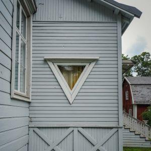 Vaaleanharmaassa puutalon seinässä kolmion mallinen ikkuna kärki alaspäin