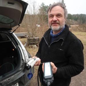 Kurt Andersson intill sin bil med bilens laddningskabel i handen.