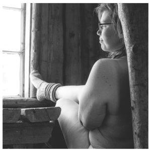 En kvinna iklädd endast stickade sockor. Vi ser henne bakifrån. Hon sitter på en bänk och tittar ut genom ett fönster. Fötterna vilar på fönsterbrädet. Bilden är svartvit.