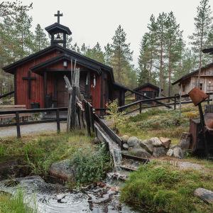 Kolme pientä mökkiä, joista yhdellä on katolla risti. Mökkien editse virtaa puro.