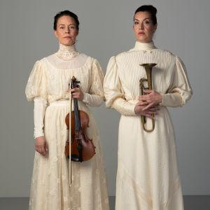 Riikka Ahokas ja Tuuli Saksala poseeraavat valkeissa mekoissa vierekkäin. Ahokkaalla on käsissään viulu ja Saksalalla trumpetti.