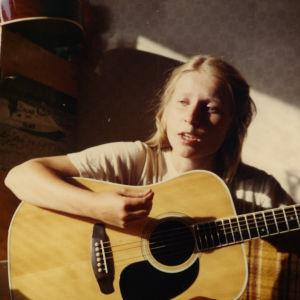 Nuori tyttö soittaa kitaraa