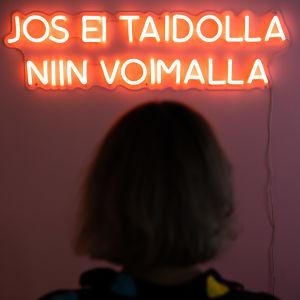 """Neonvalo seinällä, jossa lukee """"jos ei taidolla, niin voimalla""""."""