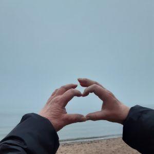 Åsa formar sina händer och fingrar till ett hjärta mot den grå dimman som ligger över havet