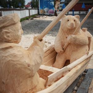 Puinen veistos, vene, jossa karhu ja mies ongella