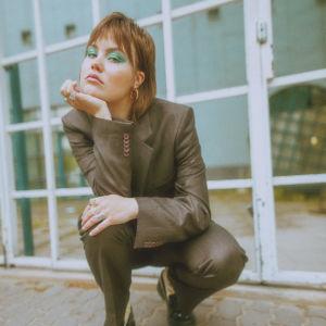 Popmuusikko Lxandra lasiseinän edessä.