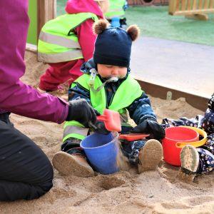 Ett litet barn leker med spade och ämbar i en sandlåda.