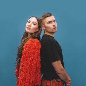 Muusikot Ida Paul ja Kalle Lindroth sinistä taustaa vasten.