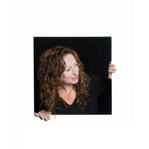 Kvinna med långt hår tittar ut genom en lucka i en vit vägg.