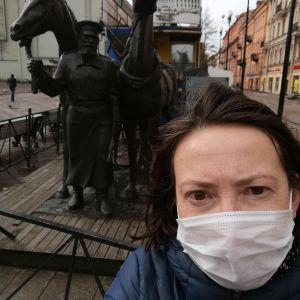 En selfie av Vera Saltanova med munskydd framför en staty i S:t Petersburg.