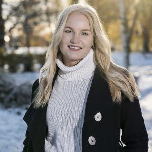 En blond kvinna i svart jacka står mot ett soligt vinterlandskap.