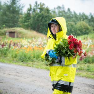 Kukkakuhhaus-kyläjuhlan työntekijä kantaa sylissään kukkakimppua, pukeutuneena keltaiseen sadeasuun.