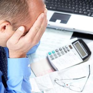 En medelålders man sitter med ansiktet i händerna vid ett skrivbord med en massa papper och kvitton samt en miniräknare och en bärbar dator.