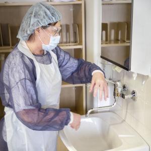 Sjukvårdare klädd i skyddsutrustning tvättar sina händer.