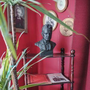 Jean Sibeliuksen rintakuva hyllyn päällä, seinällä muita muotokuvia