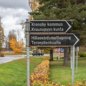 Kadunvarsikylteissä opasteet Kruunupyyn kunnantalolle sekä terveysasemalle.