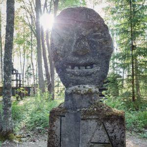 Isokokoinen kivinen veistos, jossa irvistävät kasvot, taustalla auringonsäde, ympärilä metsää