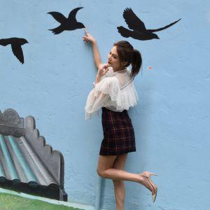 En bild på en kvinna som poserar vid och pekar på en målning av fåglar som flyger.