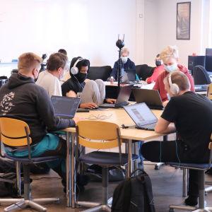 Ungdomar sitter i ett klassrum. Alla har en laptop framför sig.
