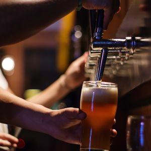 En servitör på en bar fyller ett glas med öl från en ölkran
