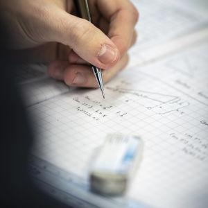 En studerande skriver matematiska formler i ett häfte.