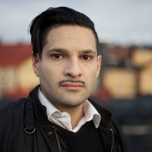 porträtt av karim jebari. han bär en mörk jacka med en vit skjortkrage som sticker upp under jackan. karim bär en tinn mustasch och har mörkt hår. bilden är tagen utomhus i kvällsljus.