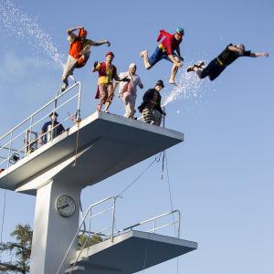 Clownhoppare hoppar ner från hopptorn på Simstadion.