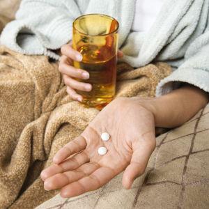 Närbild på en person som håller i värkmedicin och ett vattenglas