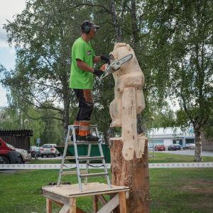Mies sahaa puistossa puuveistosta moottorisahalla, seisoo tikkailla, jotka ovat pöydän päällä