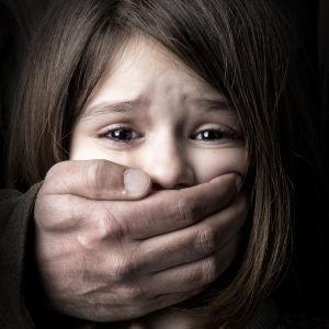 En manshand täpper till en gråtande flickas mun.