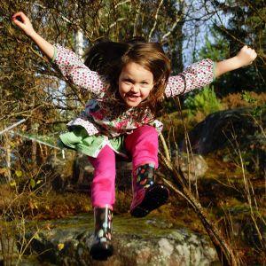 En leende flicka hoppar i skogen.