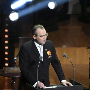 jussi Niinistö håller tal i Finlandiahuset framför två mikrofoner.